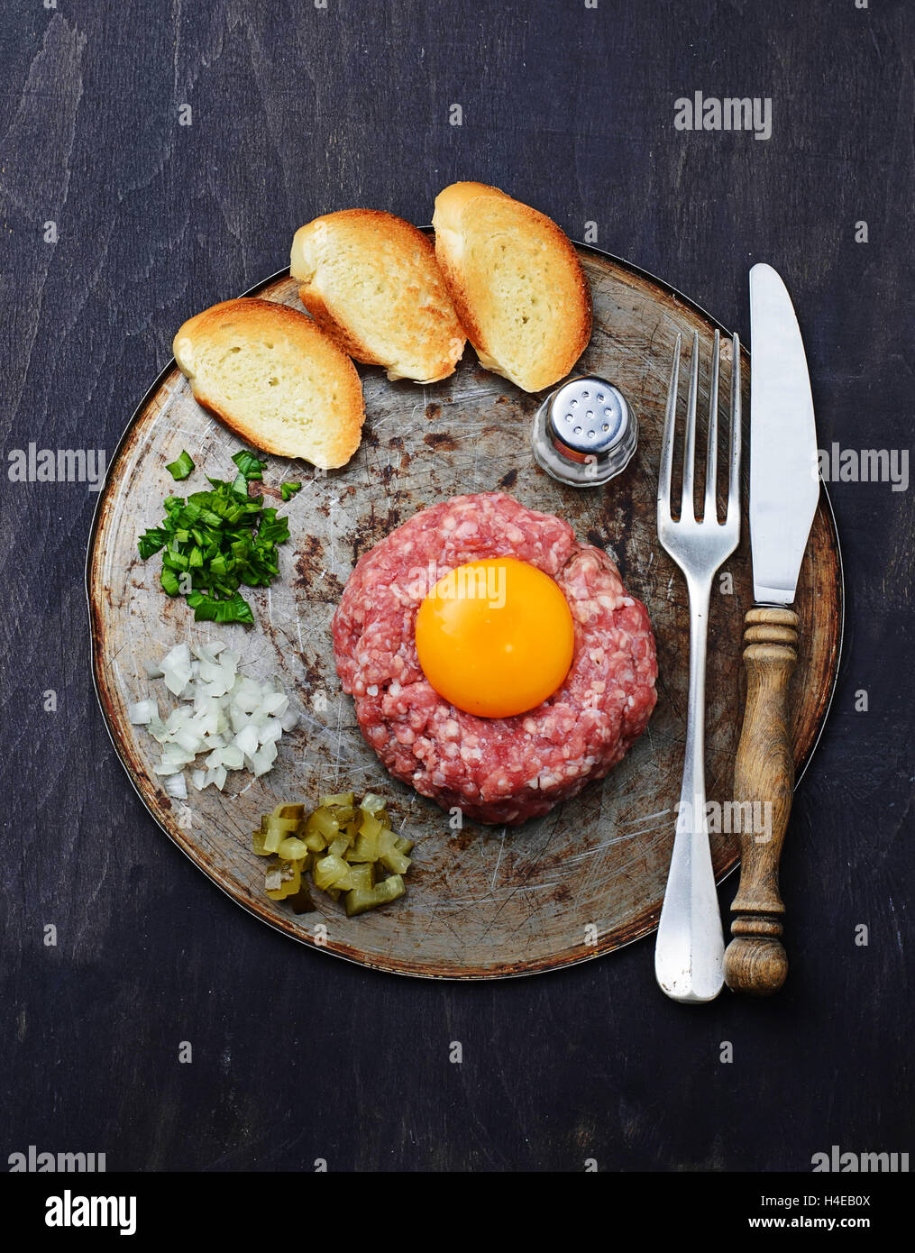 Fresh beef tartar with egg, pickled cucumber and onion. Selective focus - Stock Image