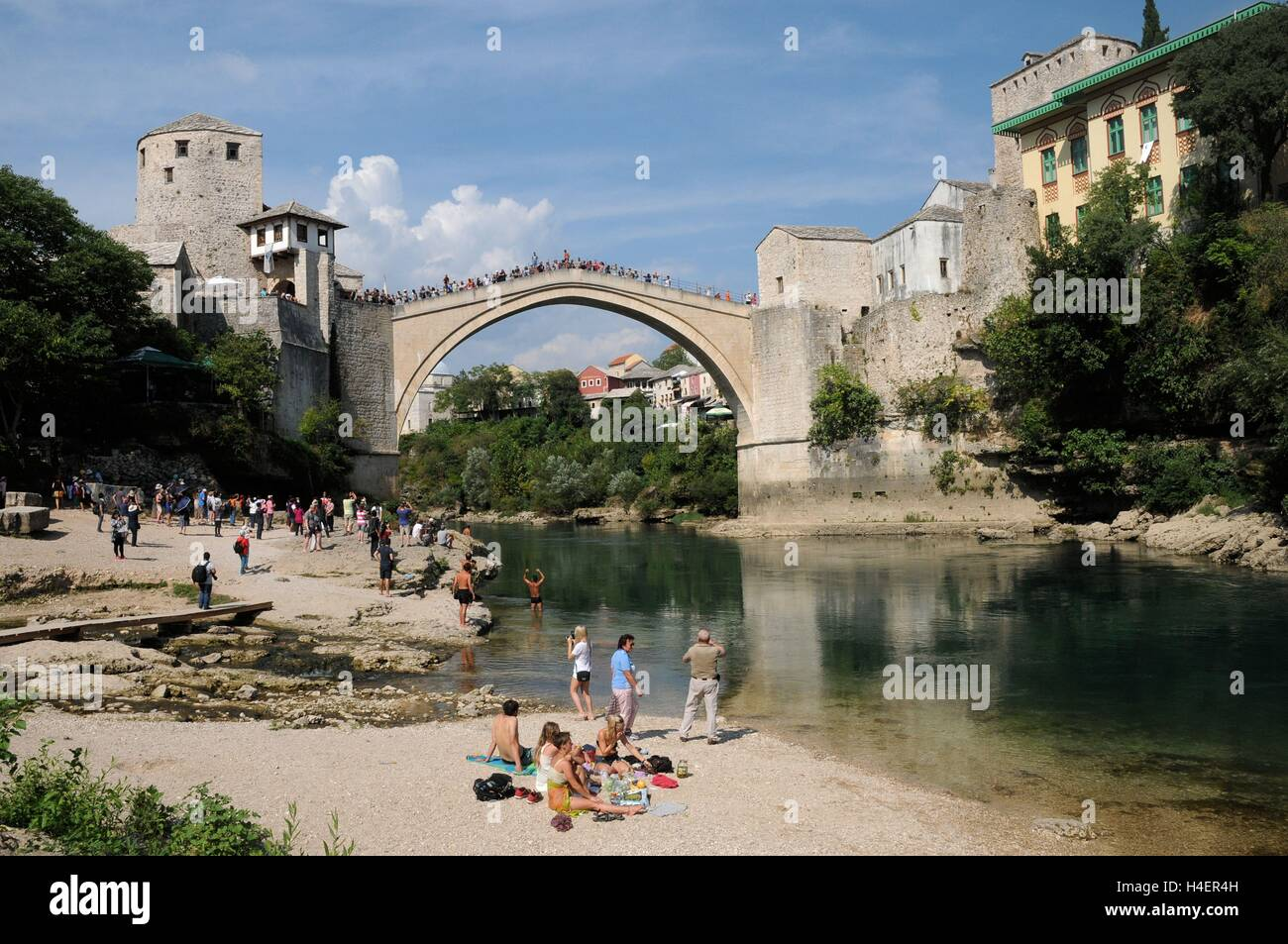 Relaxing by the riverside in front of the Stari Most bridge, Bosnia Herzegovina. Stock Photo