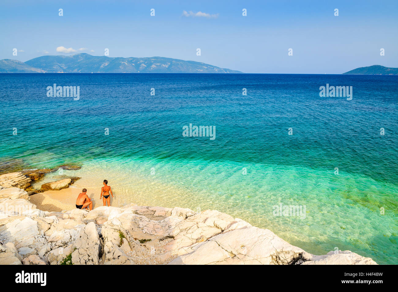 Unidentified man and woman relaxing on beautiful beach with crystal clear water on Kefalonia island, Greece - Stock Image