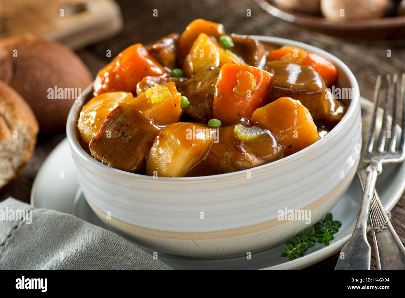 A delicious bowl of rich and hearty beef stew with potato, turnip, carrot, celery, and peas. - Stock Image