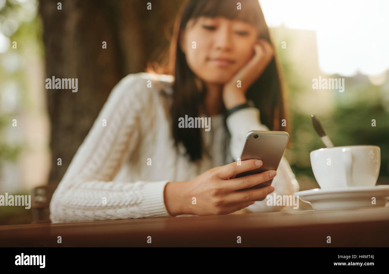 Young chinese woman looking at mobile phone in her hand while sitting at outdoor cafe. Asian female model reading - Stock Image