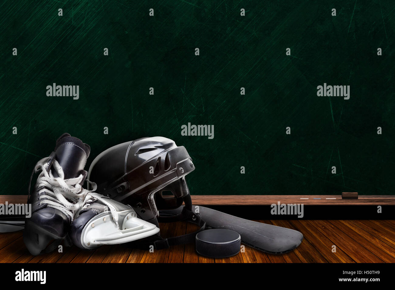 Ice hockey equipment consisting of skates, helmet, stick and puck with background chalk board copy space. - Stock Image
