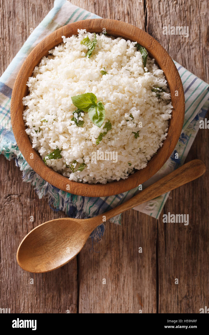 Cauliflower rice with basil close up in a bowl on the table. Vertical top view - Stock Image