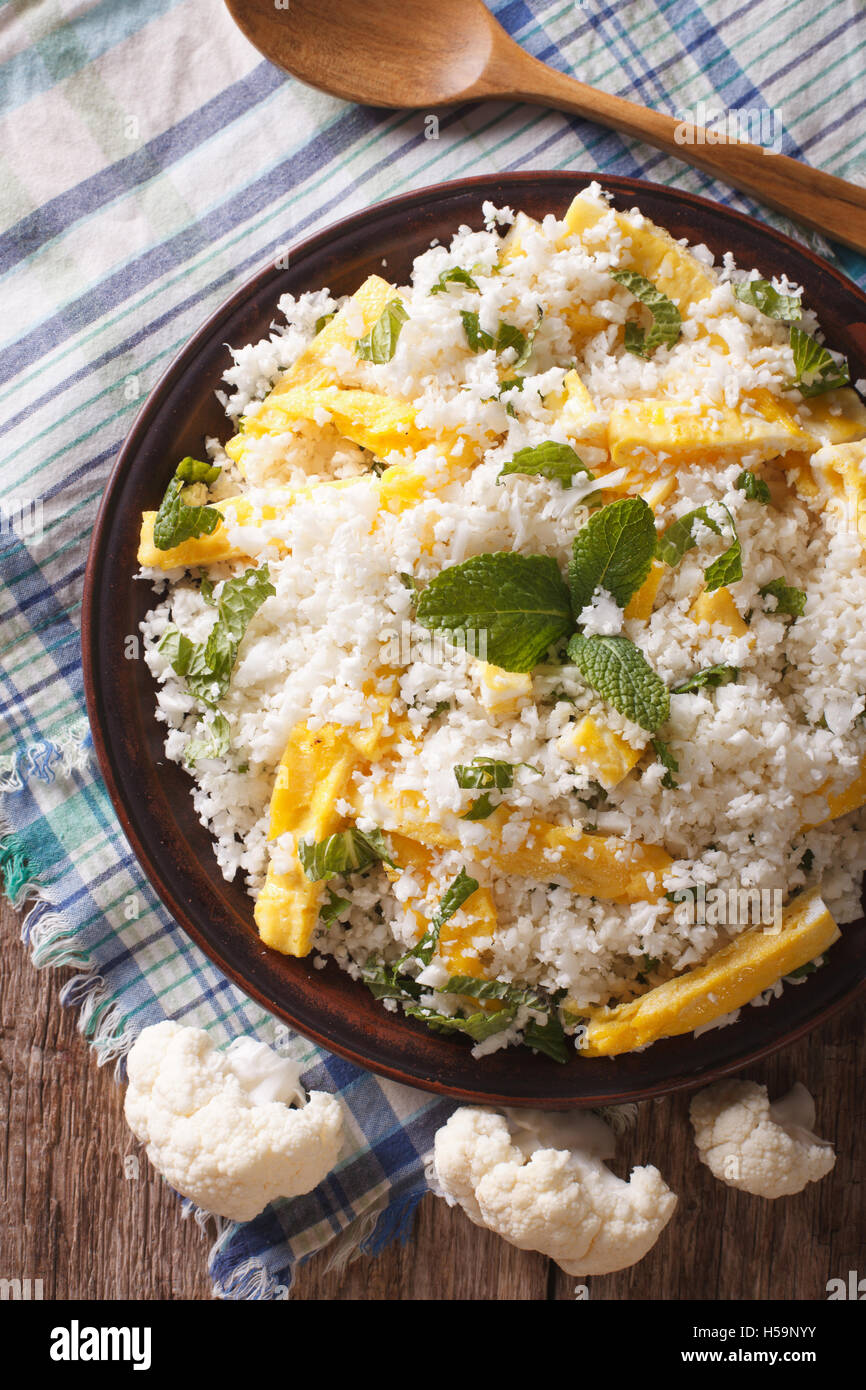 Paleo Food: Cauliflower rice with scrambled eggs and herbs closeup on a plate. vertical view from above - Stock Image