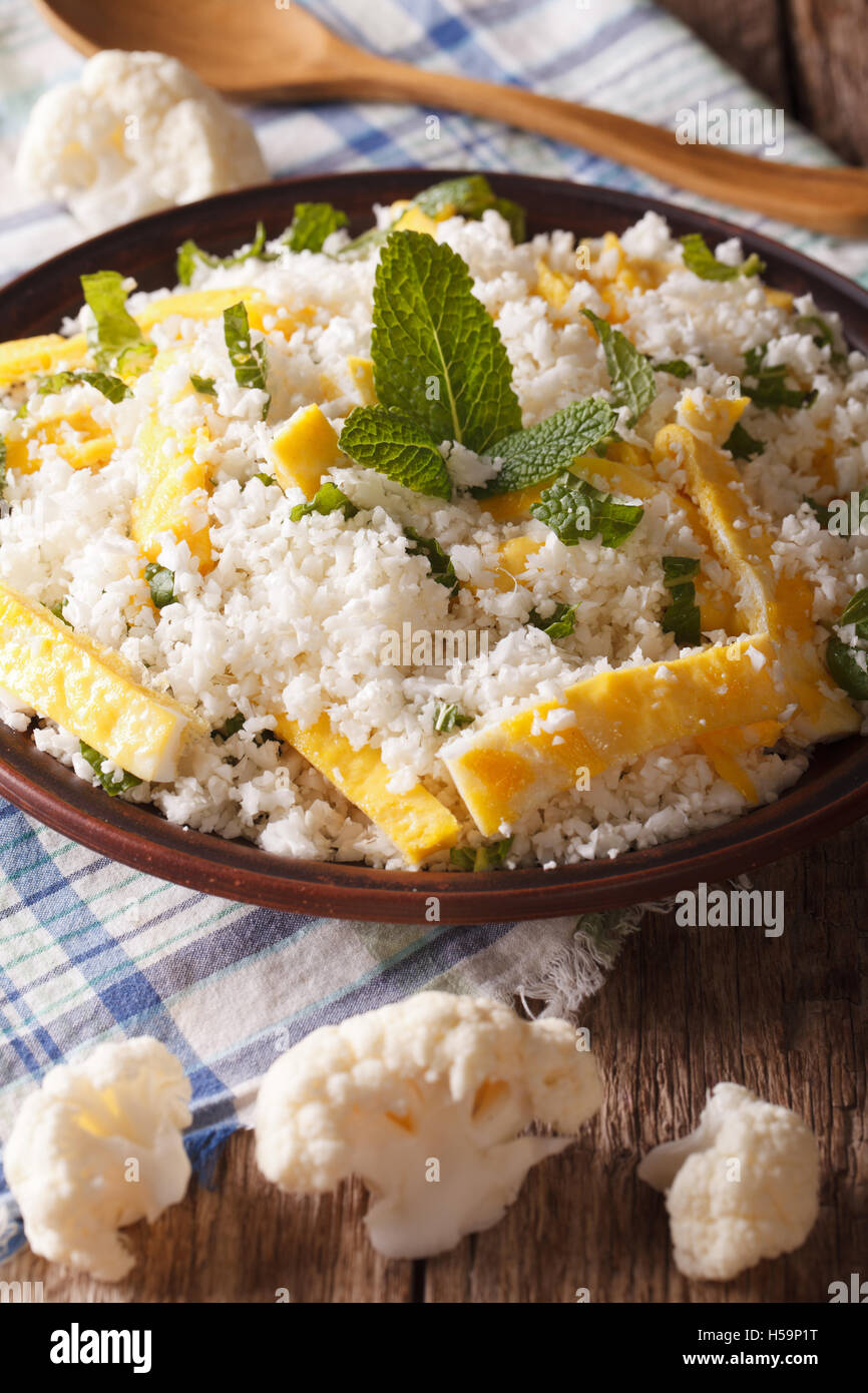 Cauliflower rice with egg and mint for paleo close-up on the table. Vertical - Stock Image