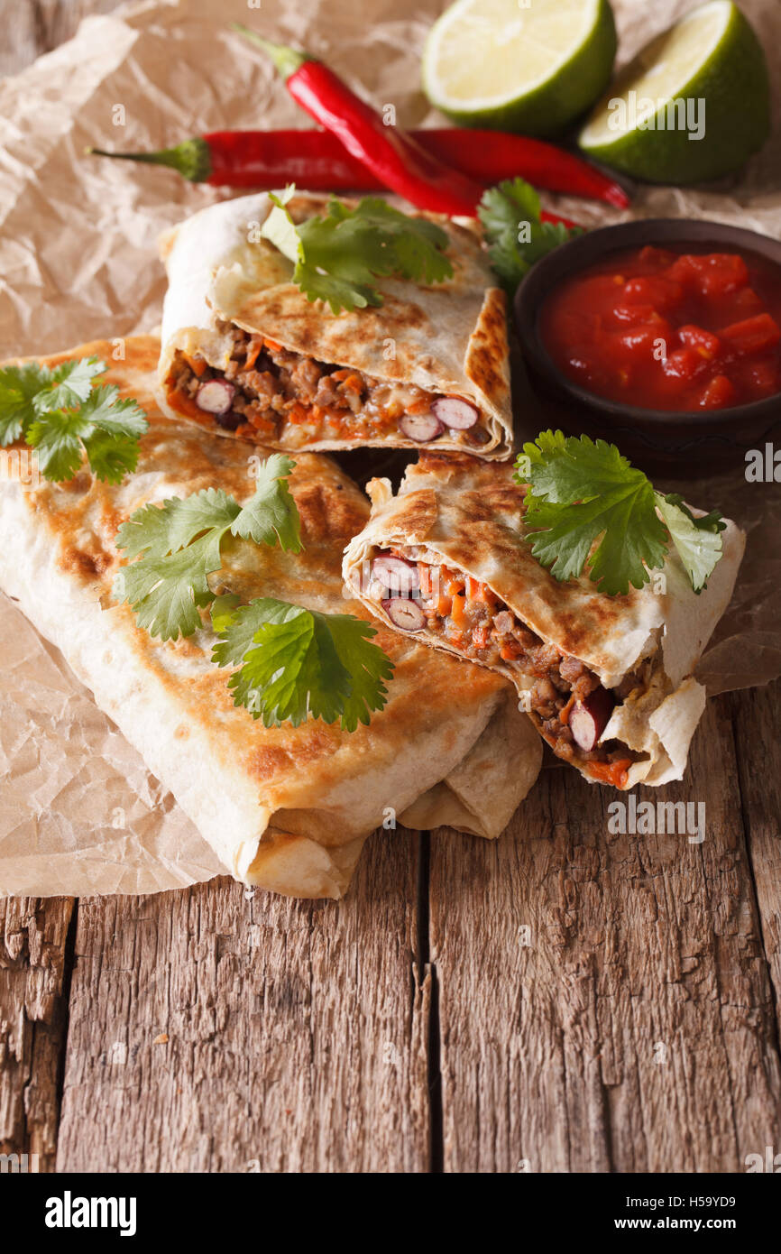 chimichanga with ground meat, beans and cheese macro on the table. Vertical - Stock Image