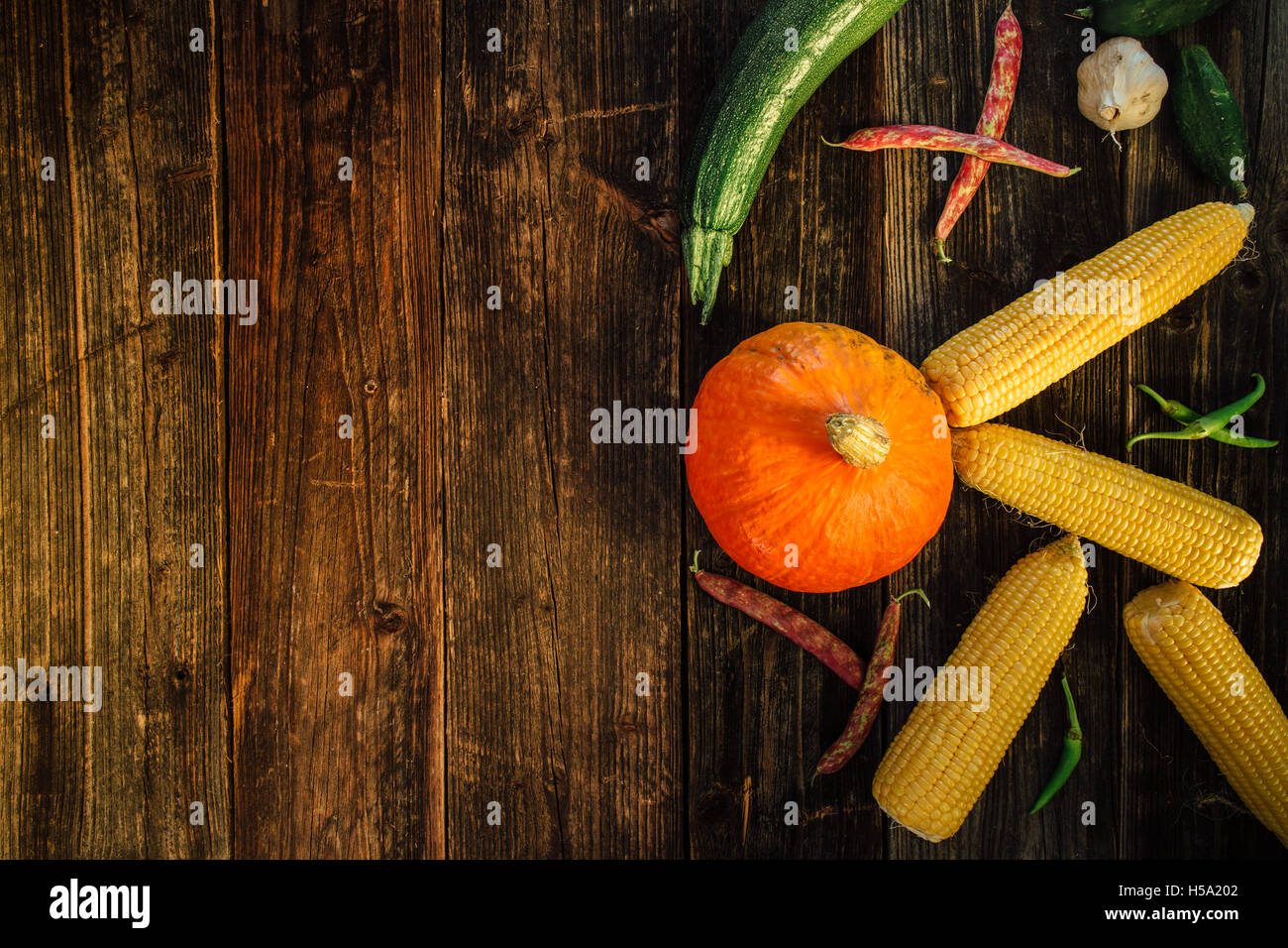 High angle view of fresh vegetables on wooden table with copy space - Stock Image