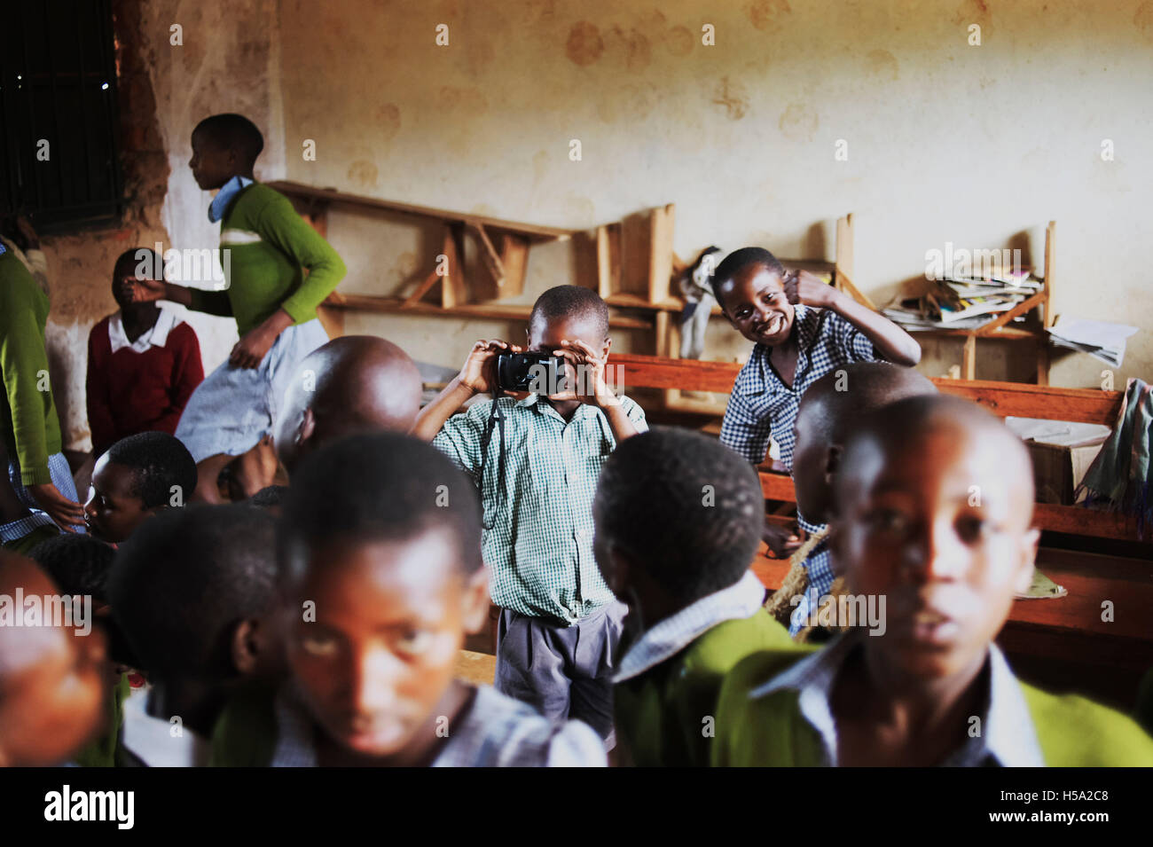 child in centre of picture is holding a camera taking a photograph during morning assembly in rural Uganda - Stock Image