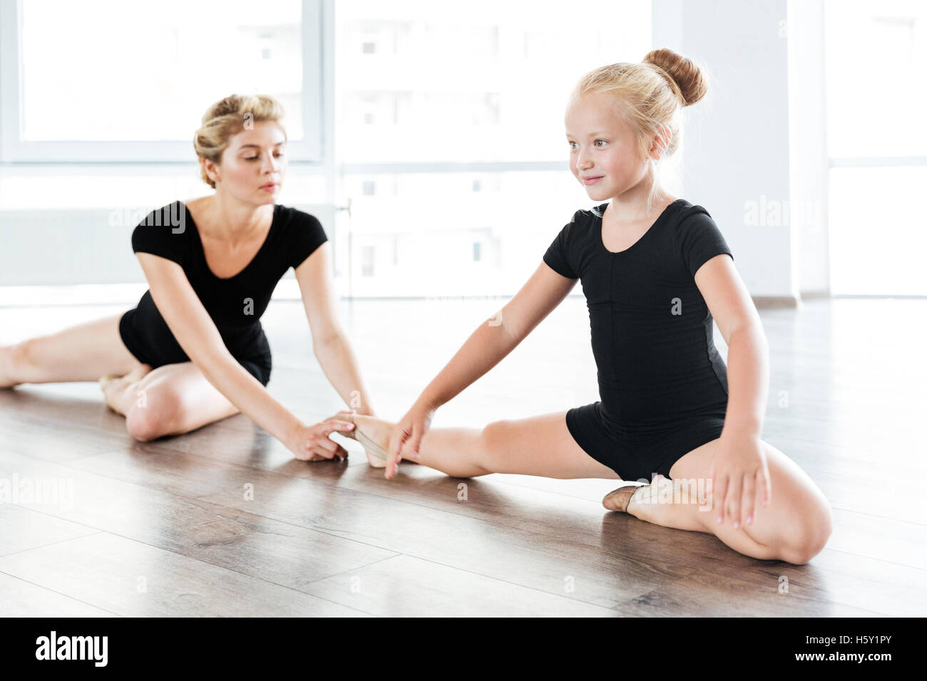 73193f3a519e Happy little girl ballerina sitting and stretching legs with teacher ...