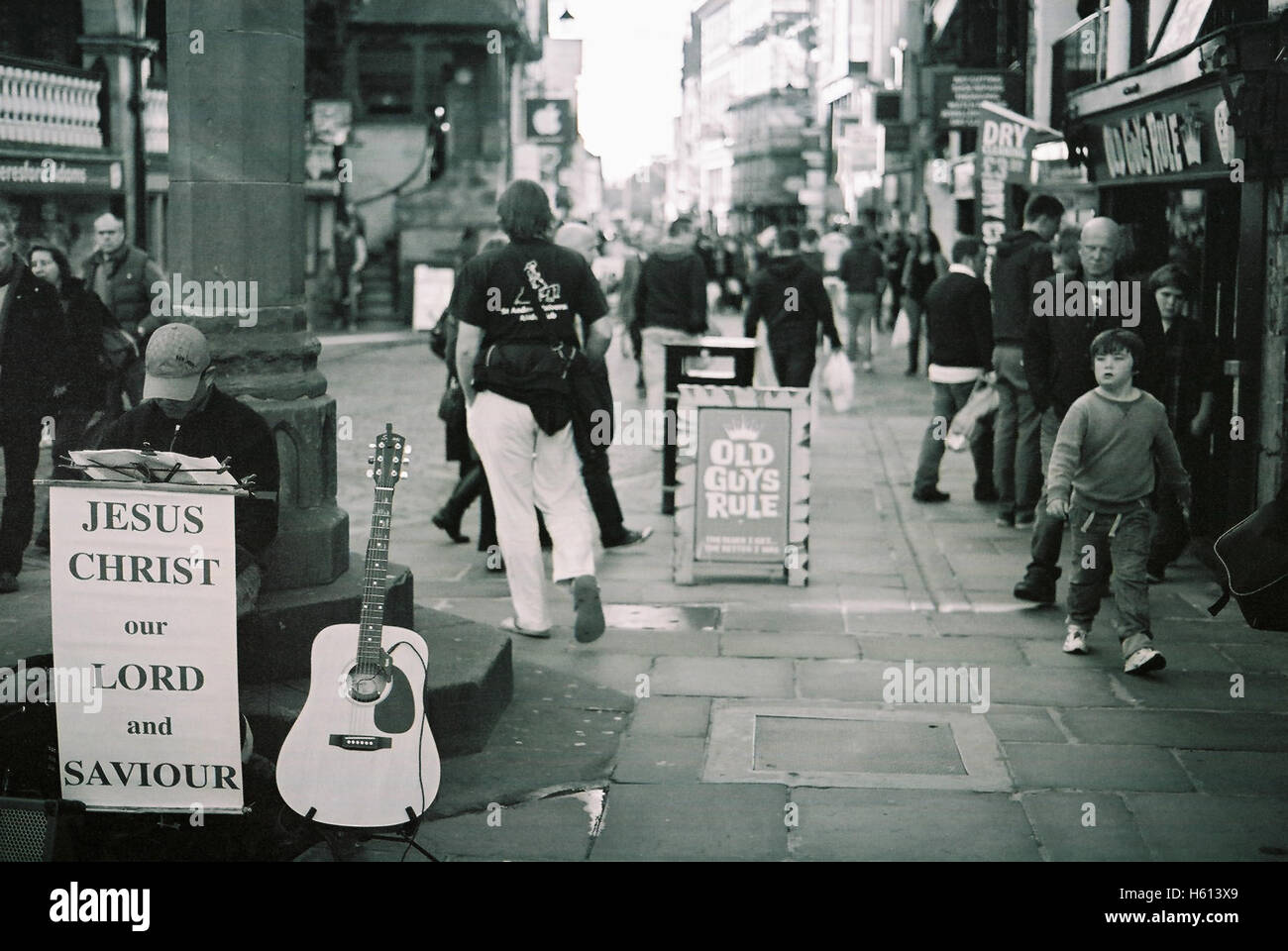 Religious busker with an old guys rule shop sign and street scene at the old cross on Watergate street, in Chester Stock Photo