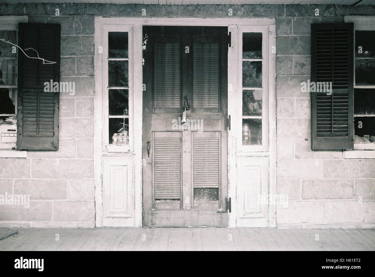 Abandoned colonial style house doorway and porch with creepy windows with wooden shutters in New Jersey USA shot Stock Photo