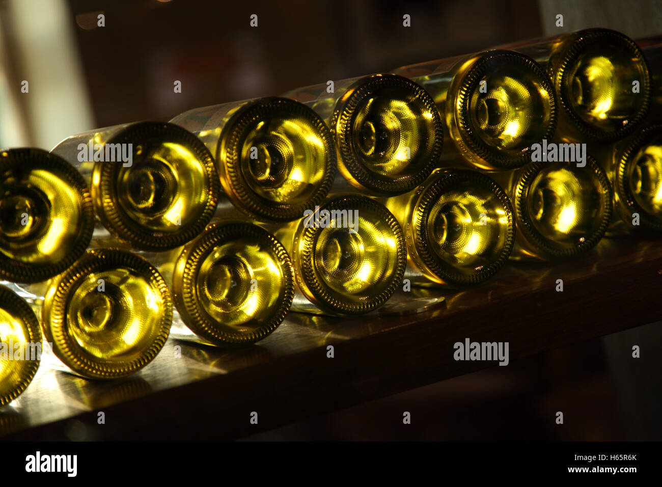 A row of wine bottles on a rack, from beneath, with light shining through Stock Photo