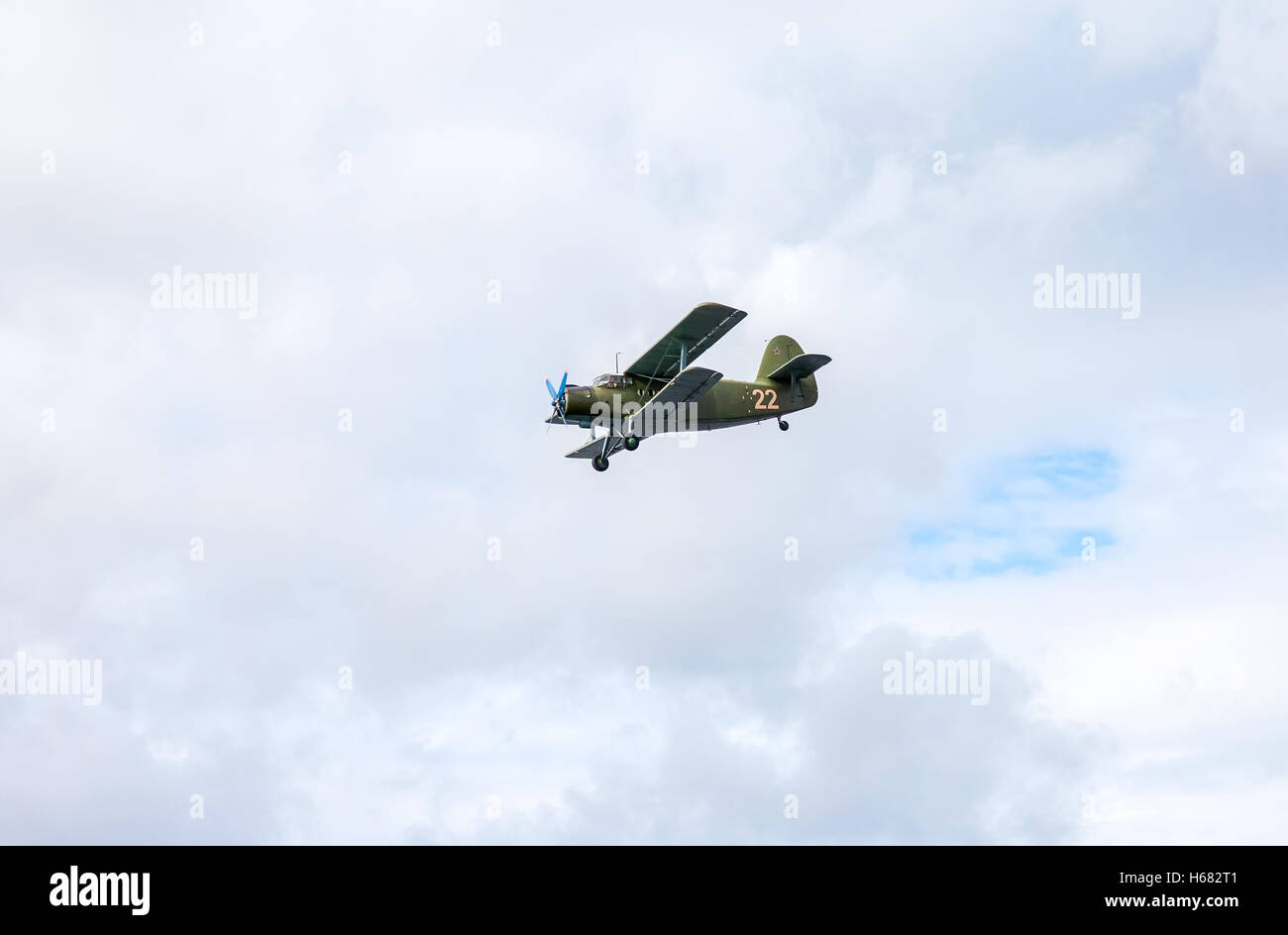The Antonov An-2 is a Soviet mass-produced single-engine biplane in flying against cloudy sky - Stock Image