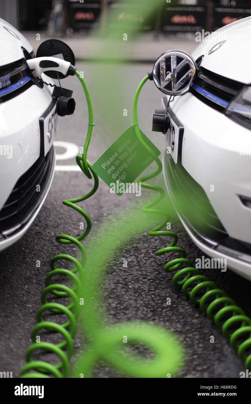 A pair of Zipcar club car-sharing Volkswagen Golf GTE plug-in petrol-electric hybrid cars being recharged on a street - Stock Image