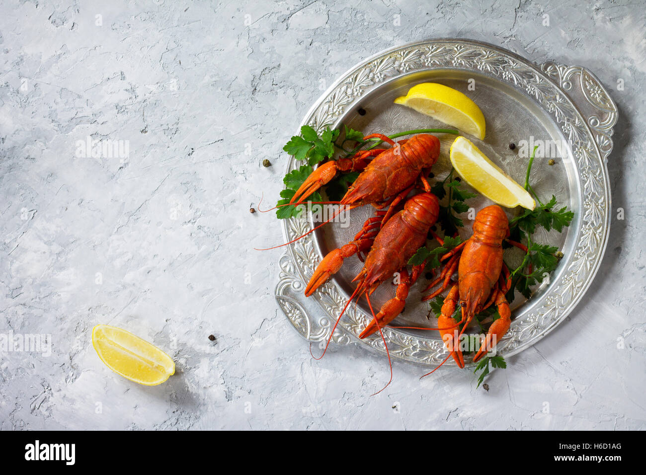 Boiled crawfish, lemon and parsley on a concrete background. Food background. The concept of healthy eating. Top - Stock Image