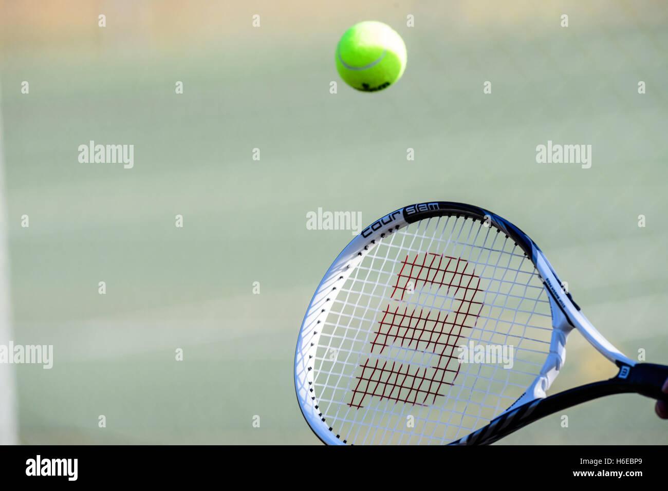 Tennis ball hitting a racket - Stock Image
