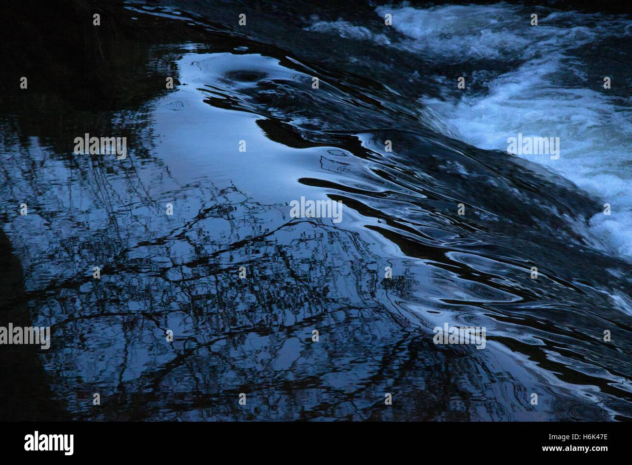 Dark blue black water passing over a weir Stock Photo