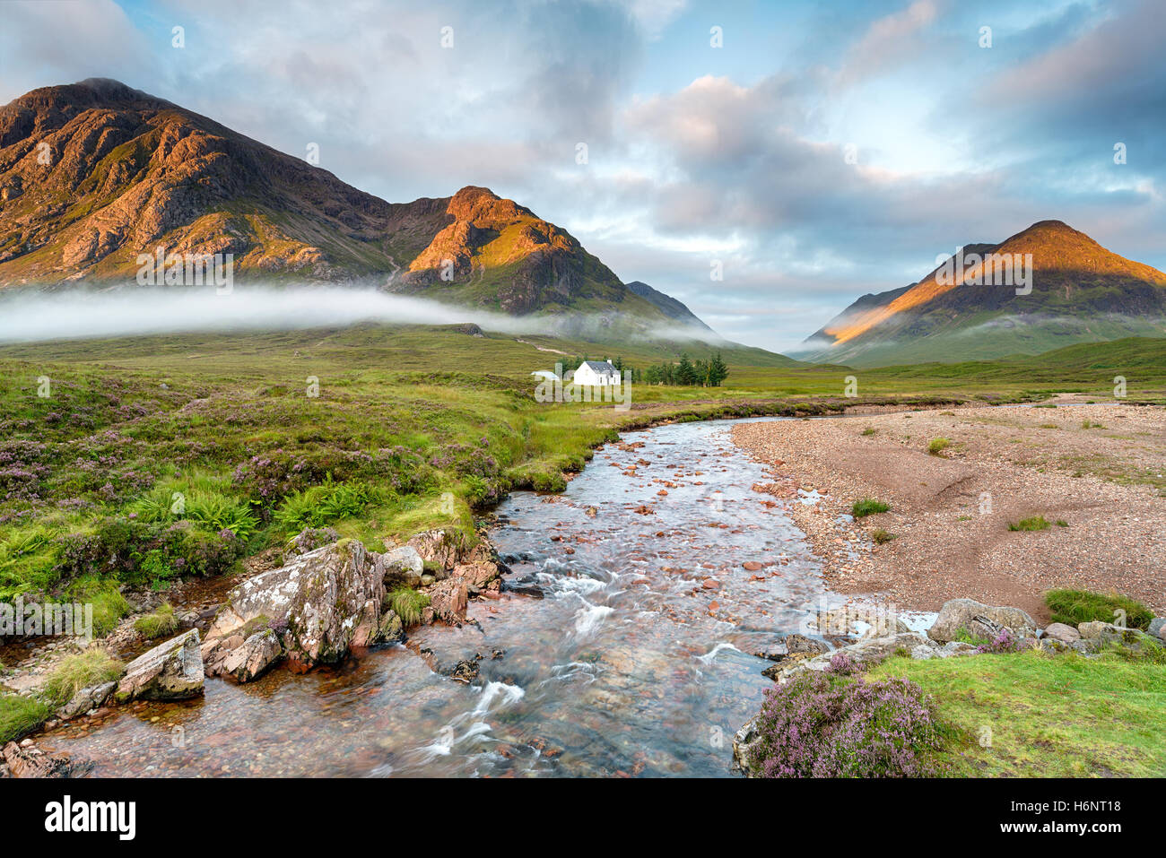 The rising sun lighting the mountain peaks at Glencoe in the Highlands of Scotland - Stock Image