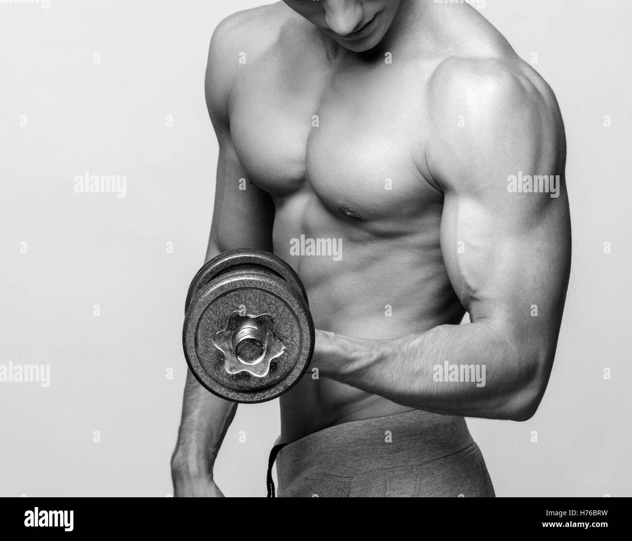 Shirtless Bodybuilder Holding Dumbell And Showing His Muscular Arms