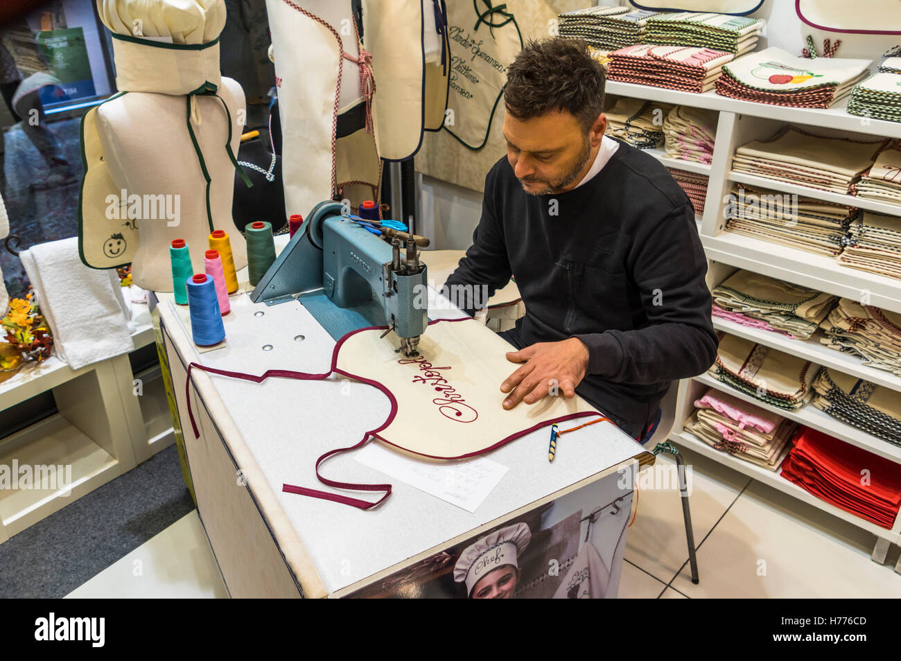 Man using a stitching machine to stitch the name 'Christoph' in script typeface on a baby bib. - Stock Image