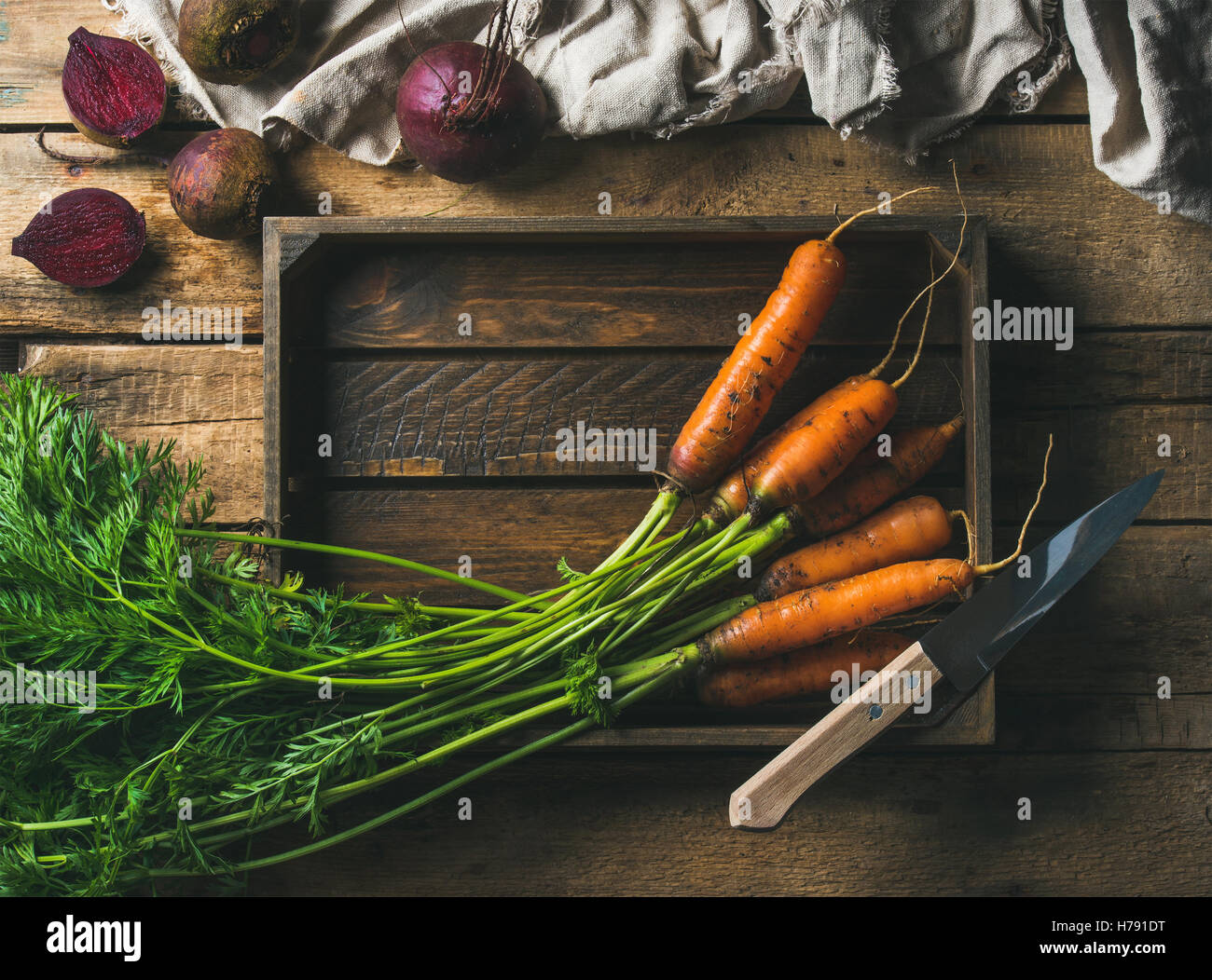 Fresh carrots and beetroots in wooden tray over rustic background - Stock Image