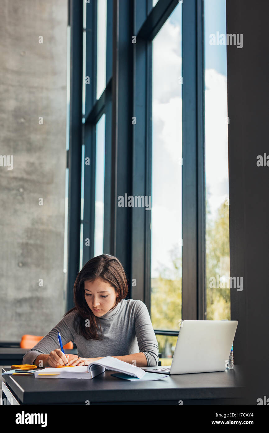 Female student taking notes from books for her study. Young woman sitting at table with books at university library. - Stock Image