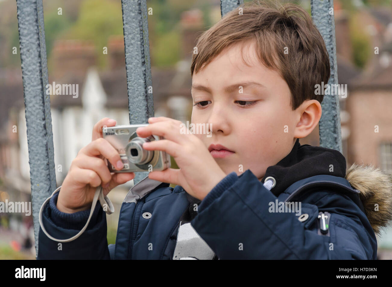 a-young-boy-taking-a-photograph-on-the-iron-bridge-at-ironbridge-in-H7D3KN.jpg