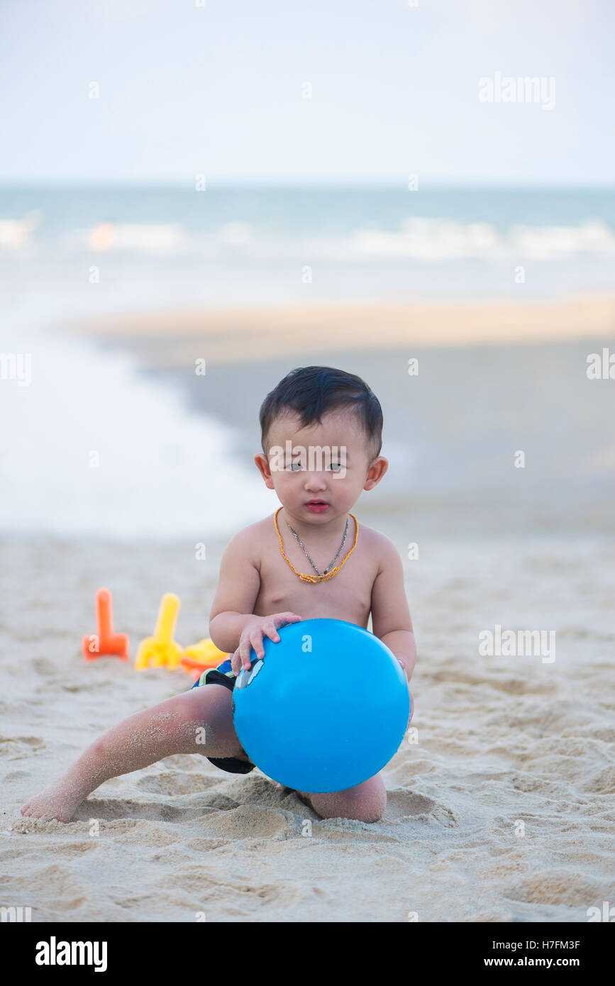 Little Asian boy 1 year old playing ball on the beach, in Thailand