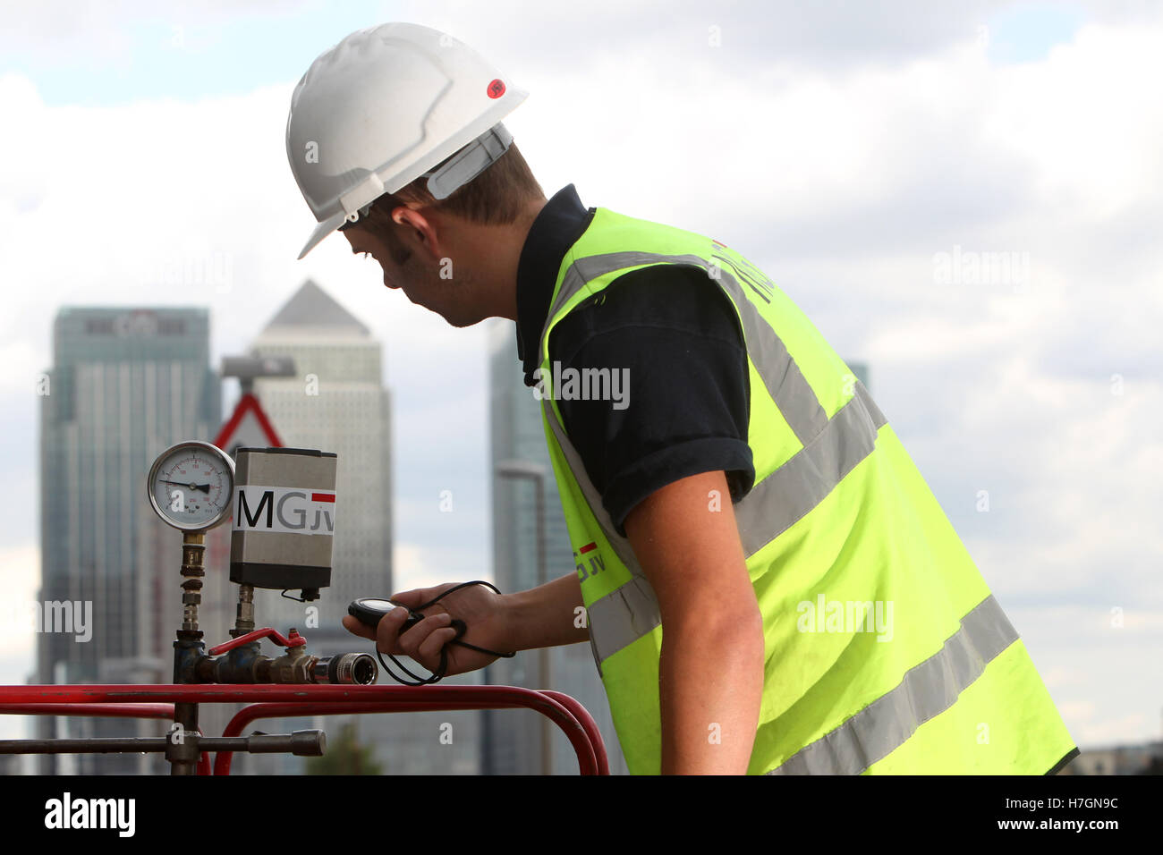 waste water workers checking valves with London skyline in background - Stock Image