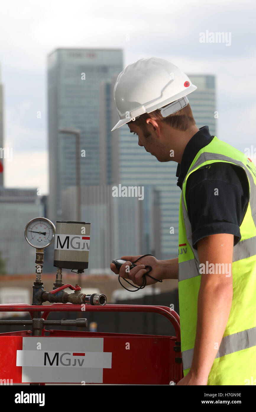 waste water worker checking valves with London skyline in background - Stock Image