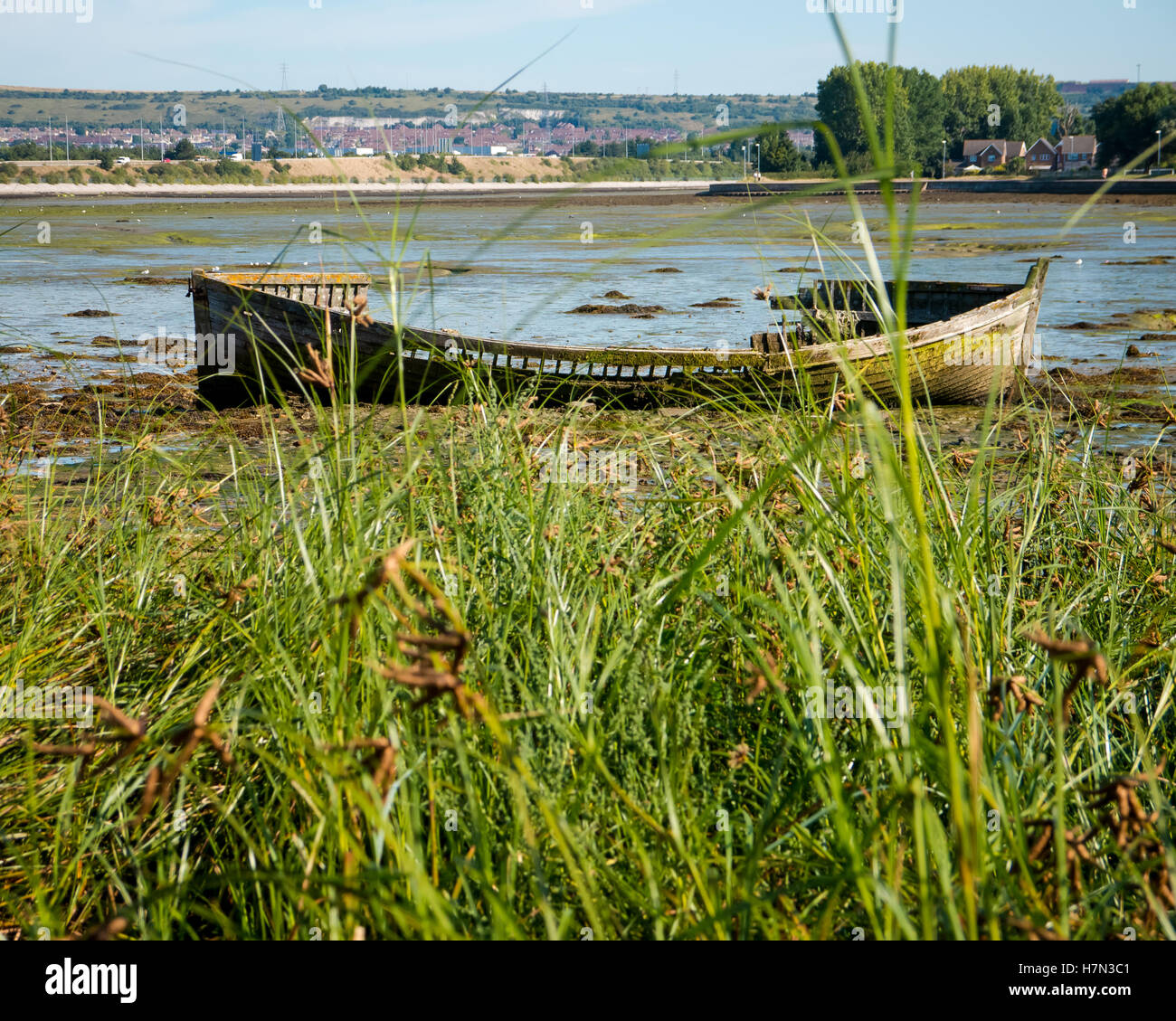 a-rotting-boat-on-the-shore-of-tipner-lake-in-portsmouth-harbour-england-H7N3C1.jpg