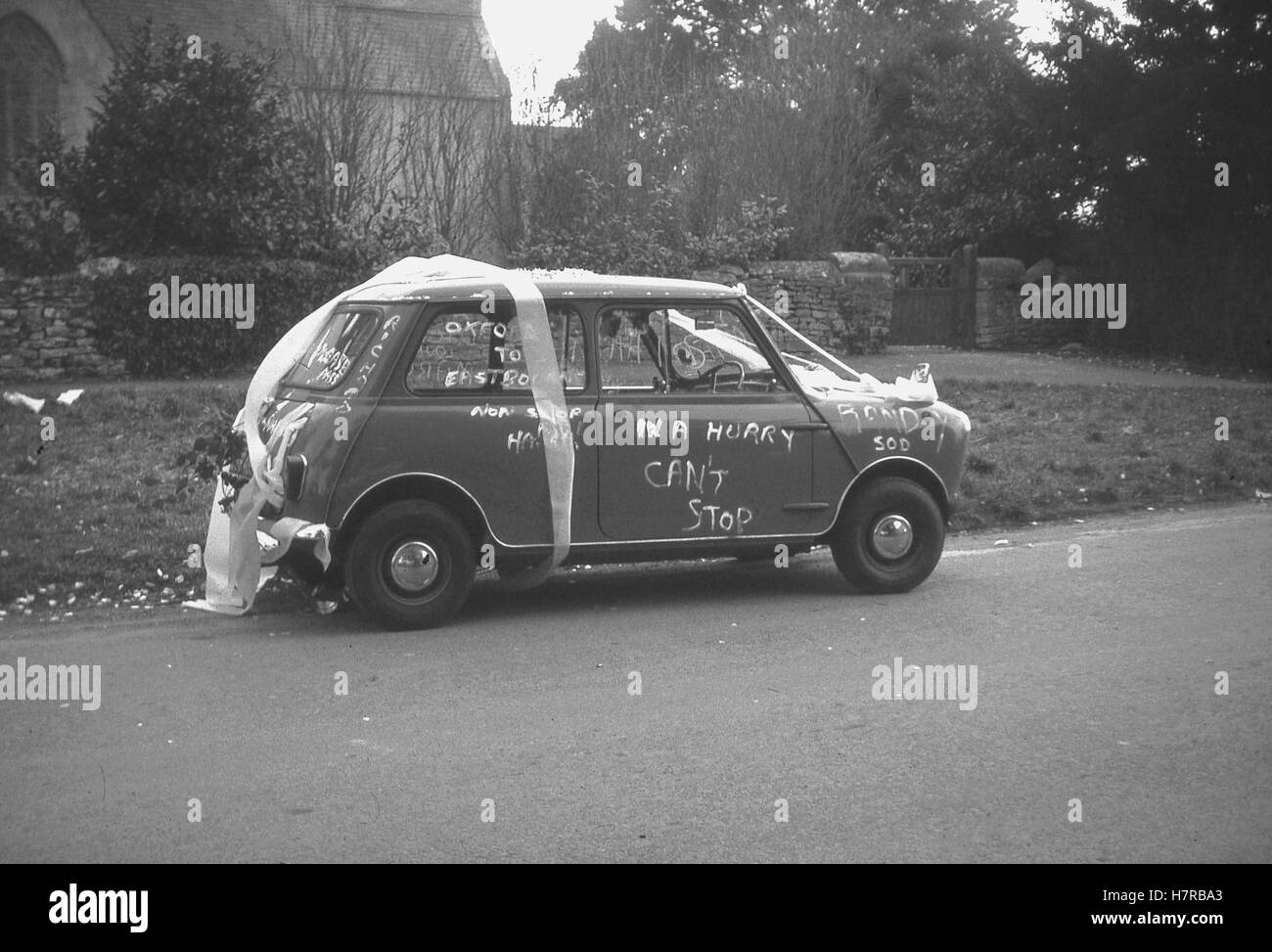 1960s, historical,  a married couple's mini car decorated with ribbons and fun slogans at the wedding outside - Stock Image