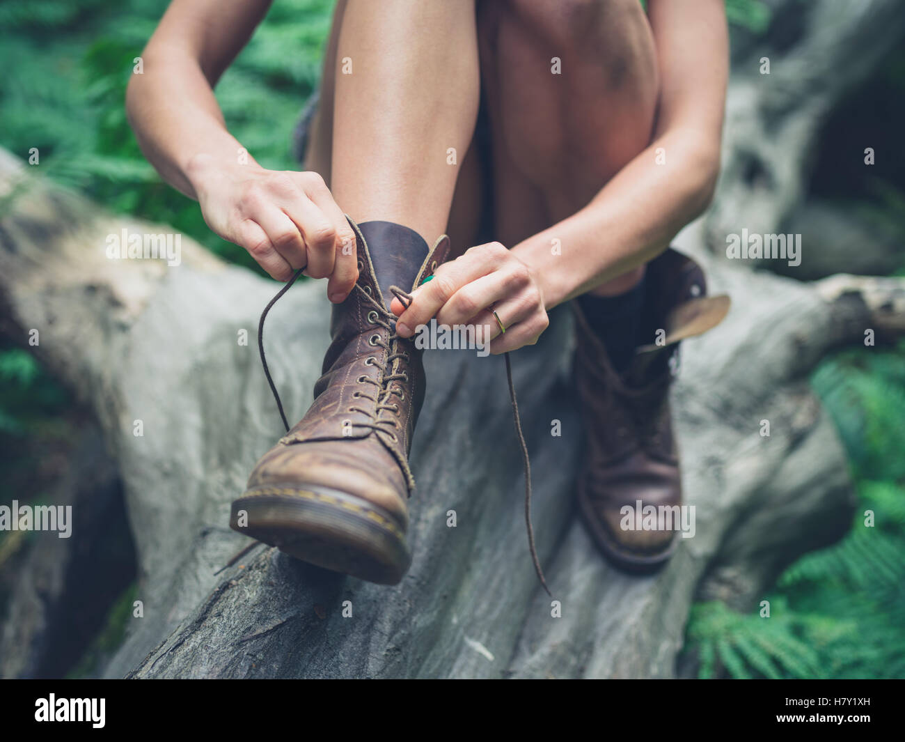 A young woman is sitting on a log in the forest and is tying her boots - Stock Image