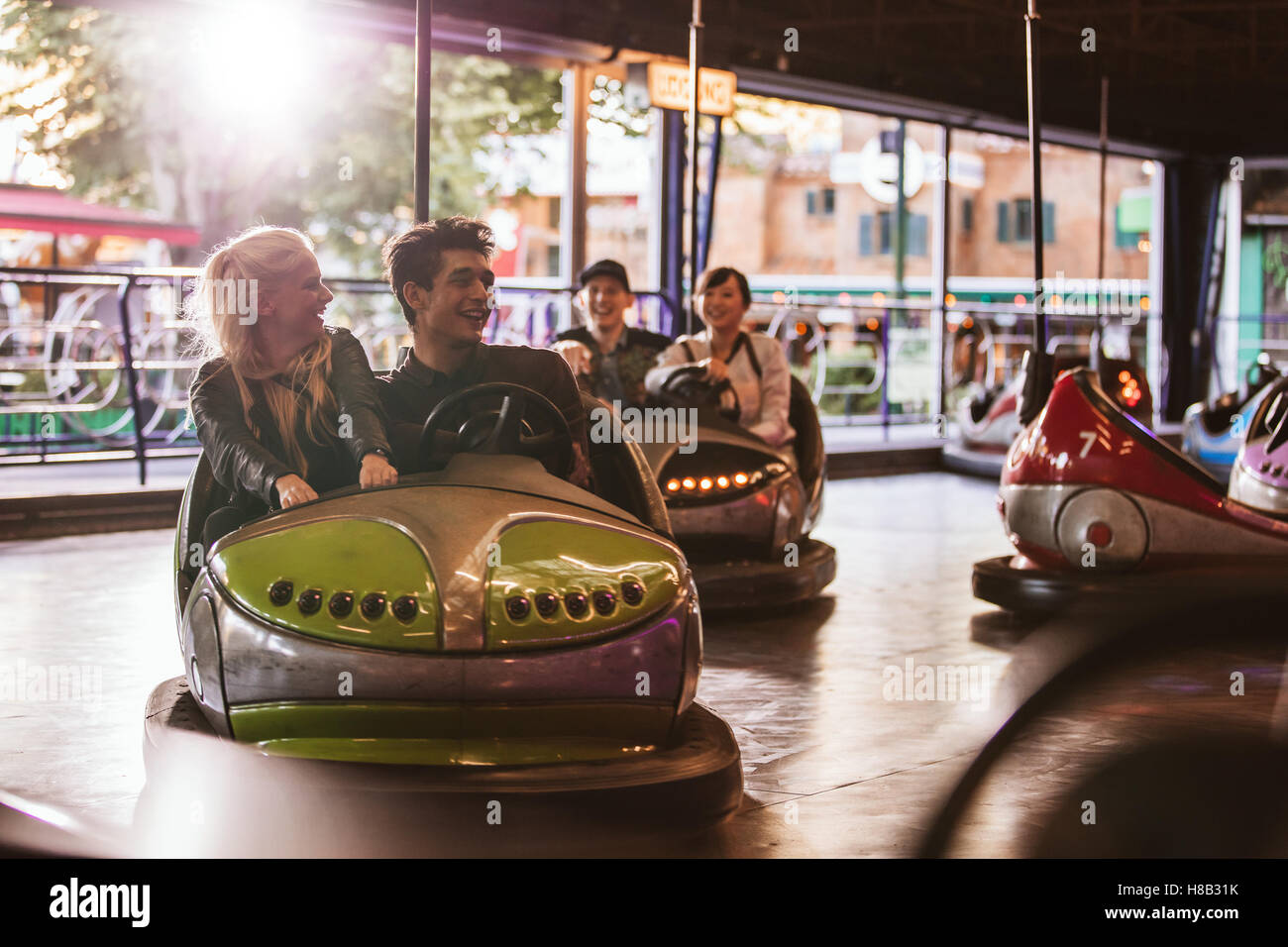 Young people driving bumper car at fairground. Young friends having fun riding bumper car at amusement park. - Stock Image