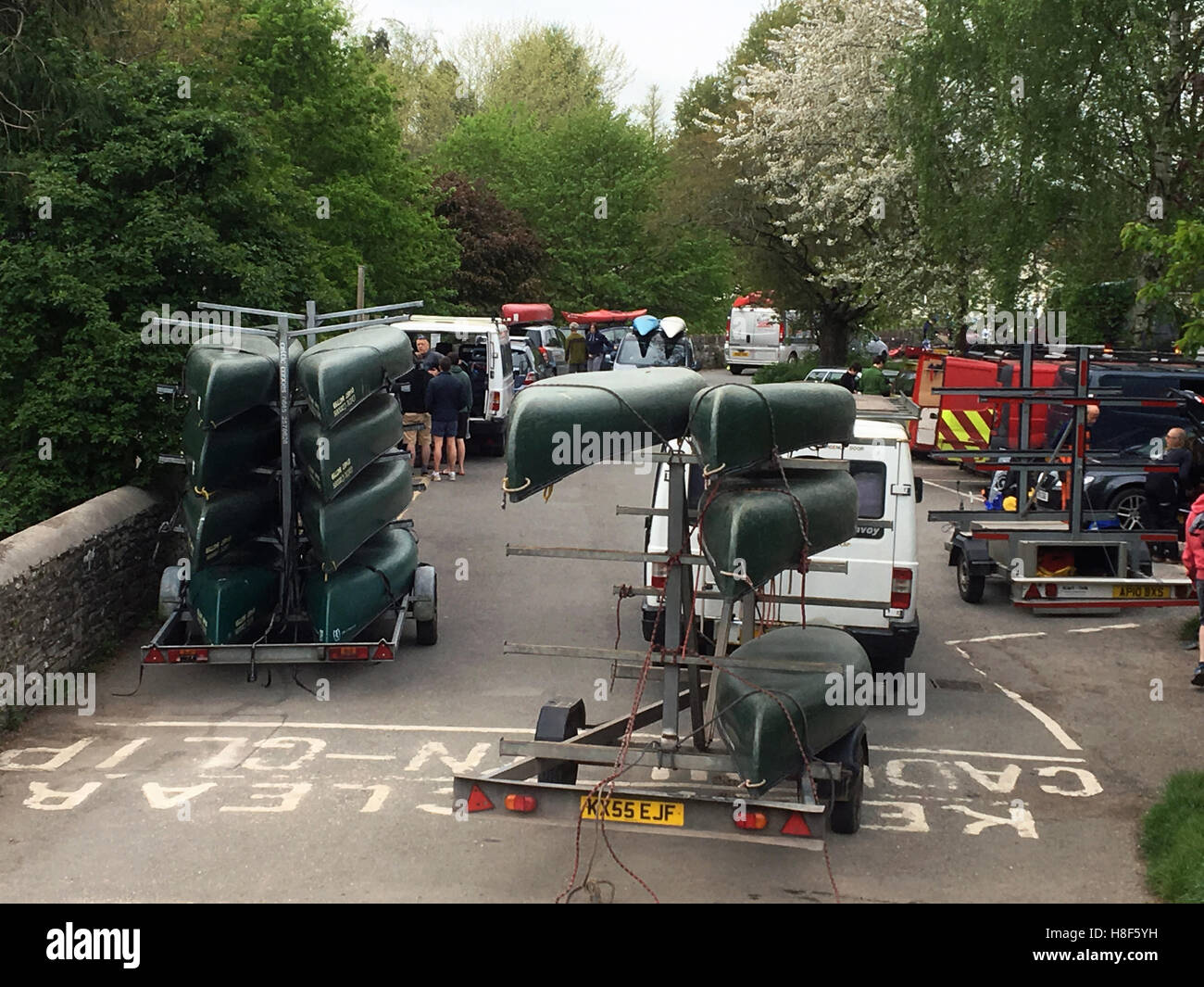 Canoe hire companies queue up to unload in a riverside car park at Glasbury Powys Wales UK - Stock Image