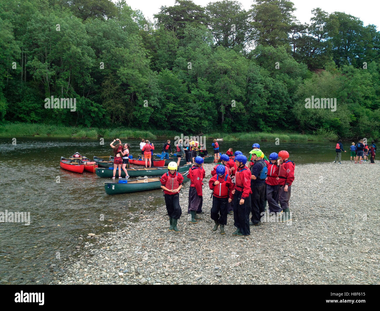 Group of teenagers canoeing on River Wye at The Warren Hay-on-Wye Powys Wales UK - Stock Image