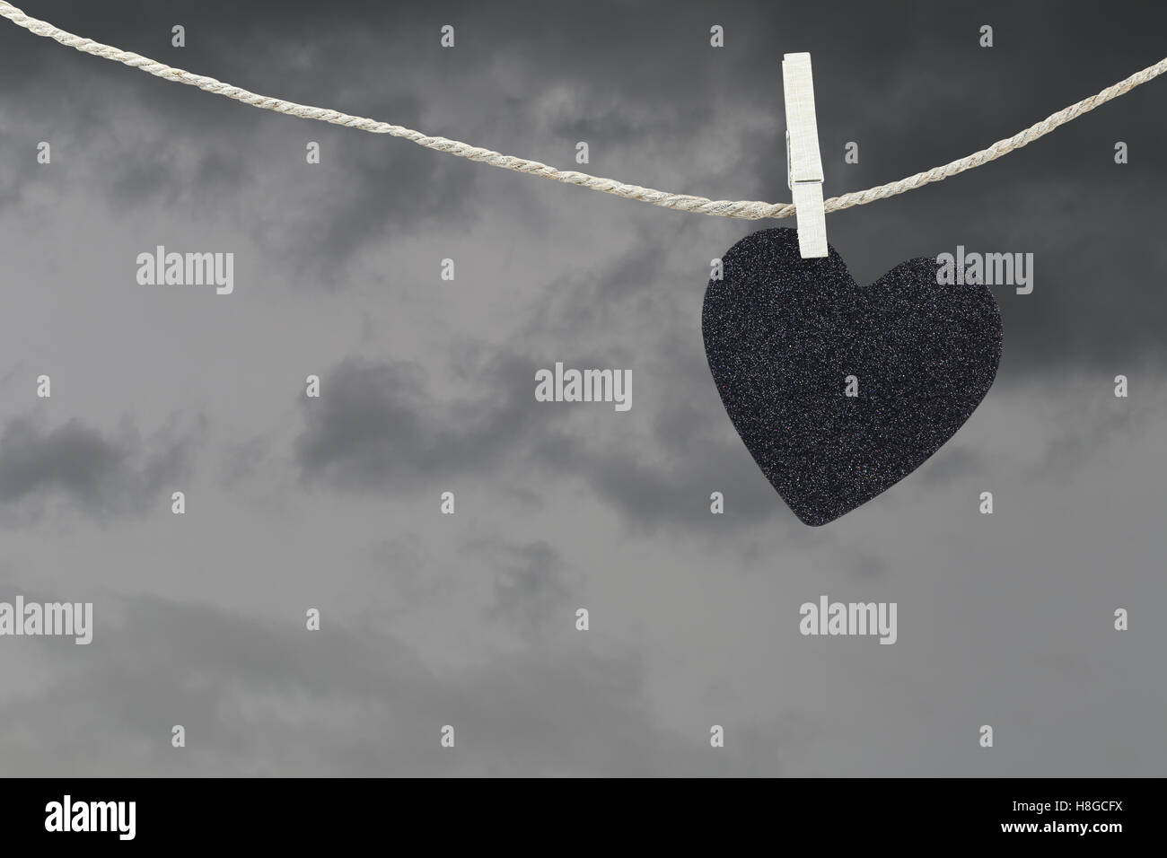 Black Heart paper hanging on a brown hemp rope on rain clouds background,Concepts about unrequited love and heartbreak. - Stock Image