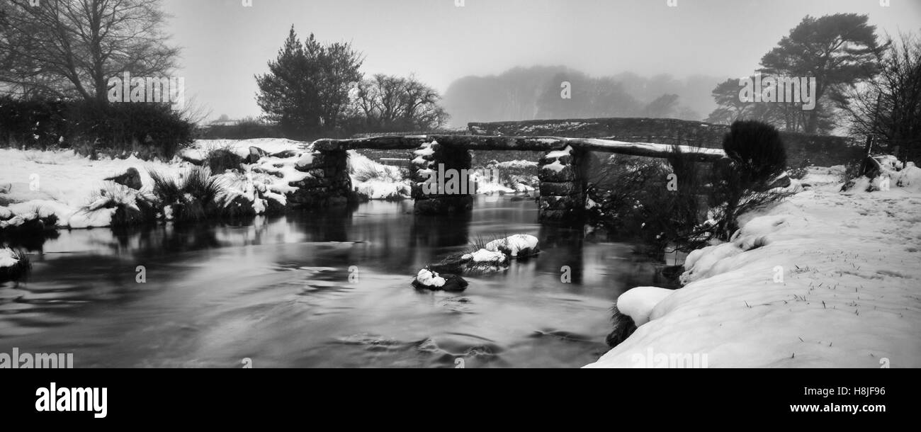 Two Bridges on Dartmoor in winter with a misty backdrop and snow covered banks and an ice cold East Dart River. - Stock Image