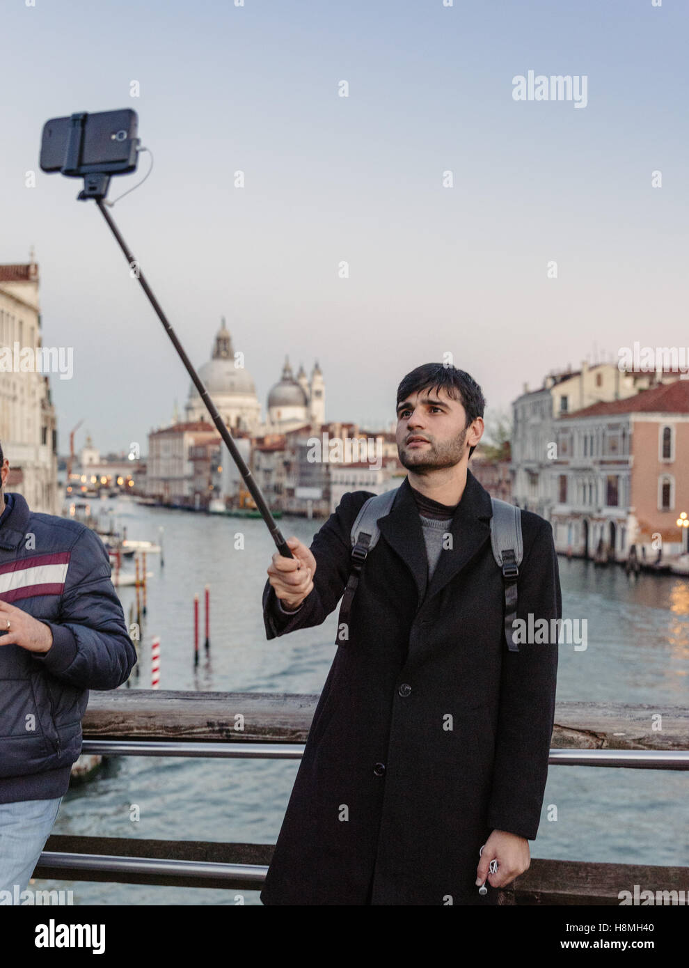 a-young-man-is-taking-a-selfie-in-venice-a-popular-tourist-destination-H8MH40.jpg