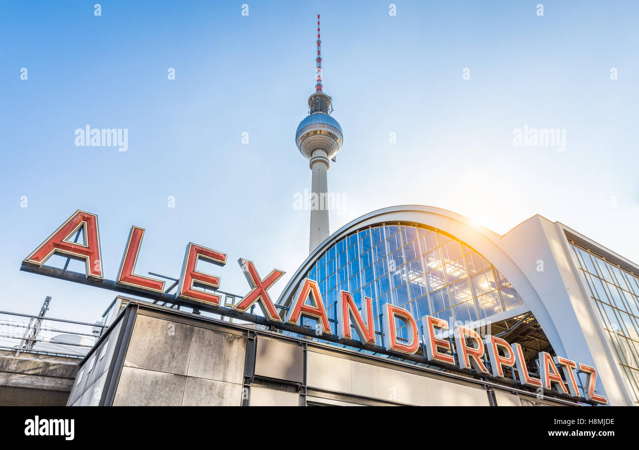 Classic wide-angle view of Alexanderplatz neon sign with famous TV tower and train station at sunset, Berlin, Germany - Stock Image
