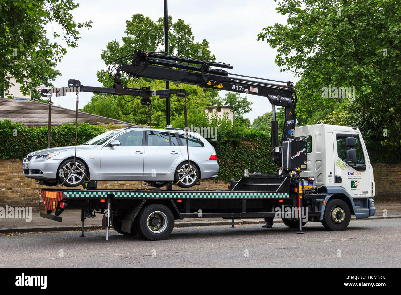 An illegally parked car being hoisted onto a lorry for removal, Hampstead Lane, London, UK Stock Photo