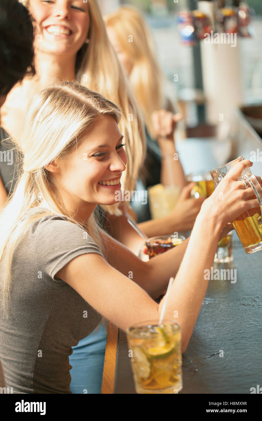 Blonde women drinking beer in bar - Stock Image