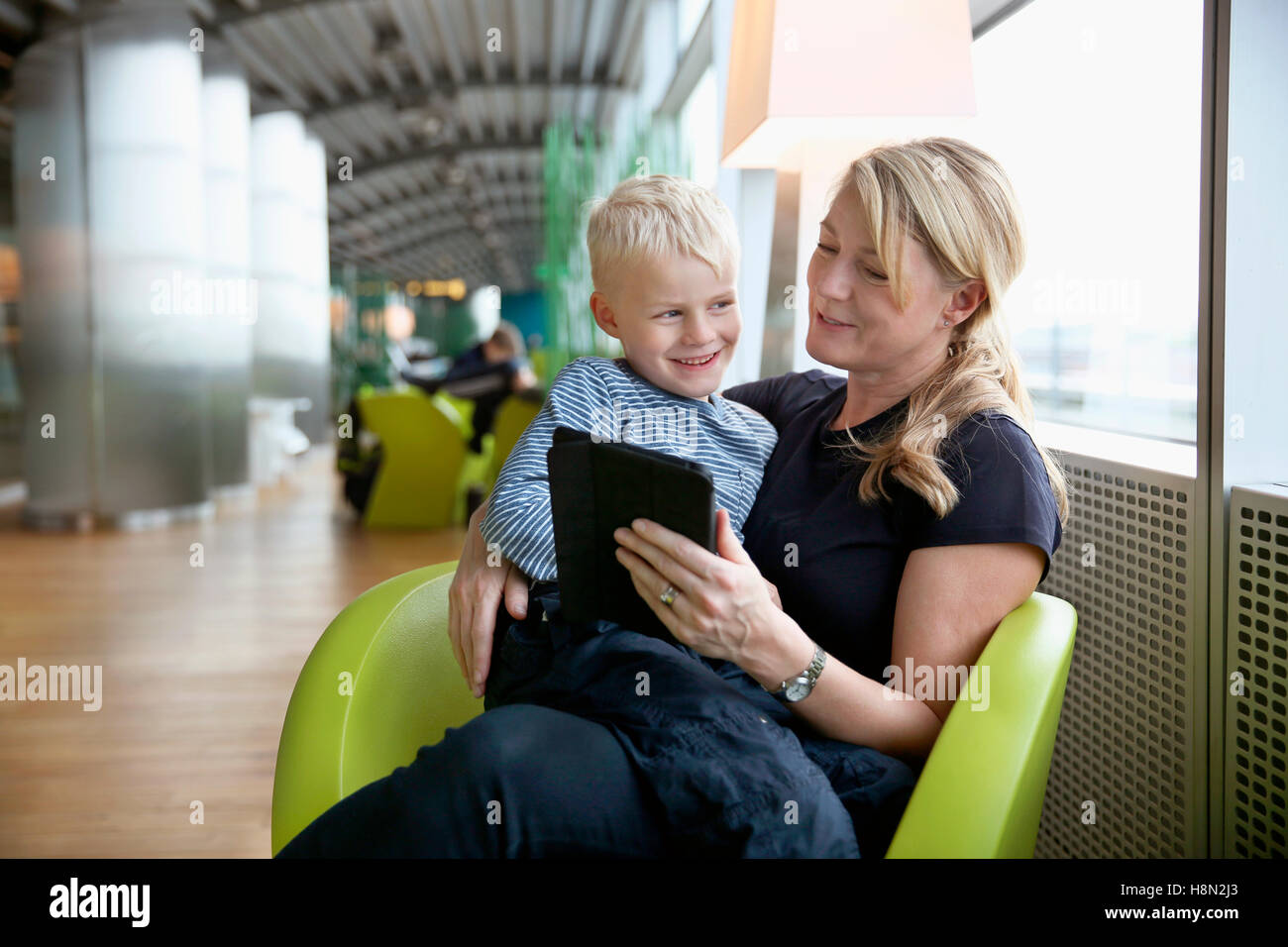 Mature woman sitting at airport hall and using tablet with boy (6-7) sitting on her lap - Stock Image