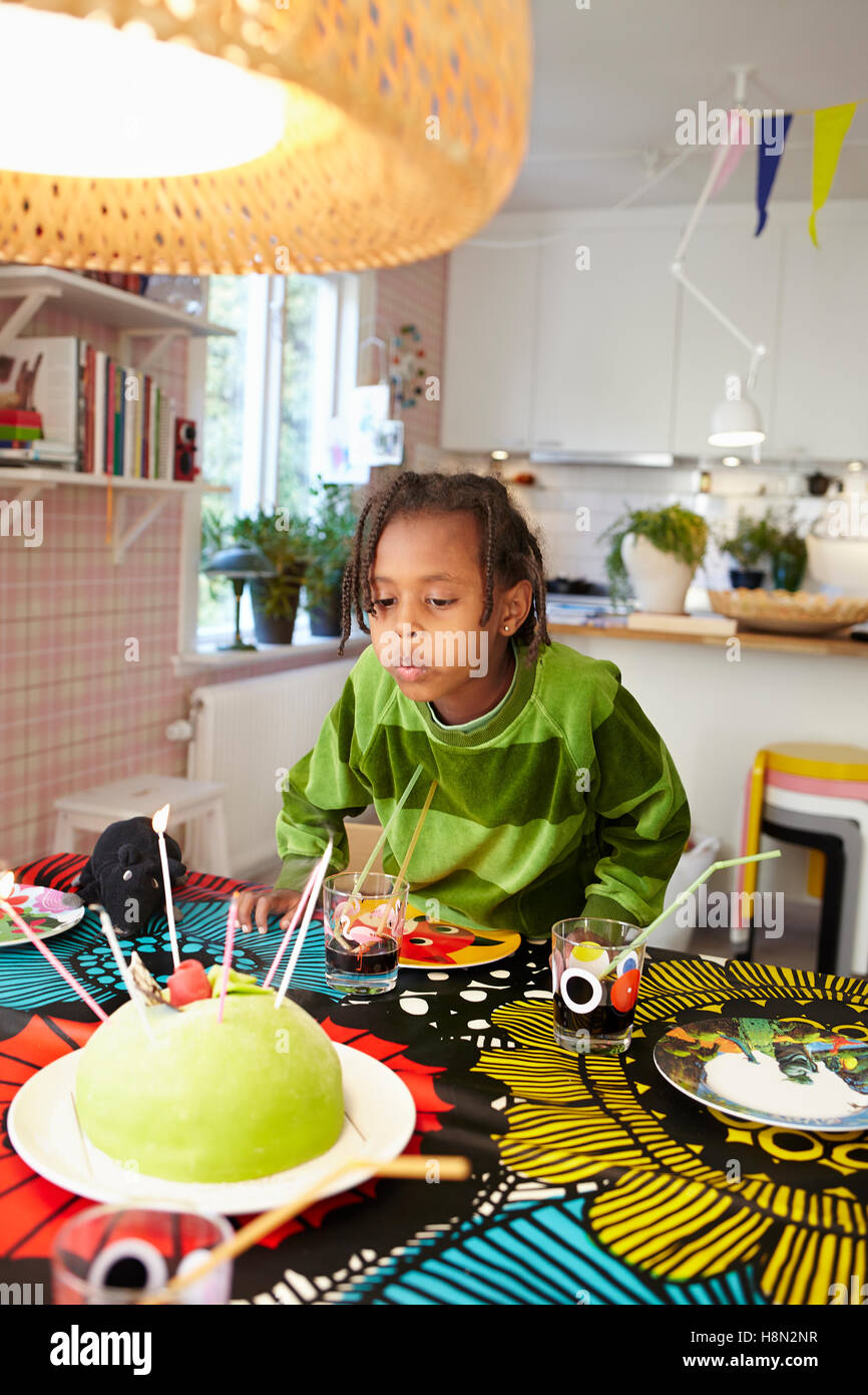 Girl (6-7) blowing candles on birthday cake - Stock Image