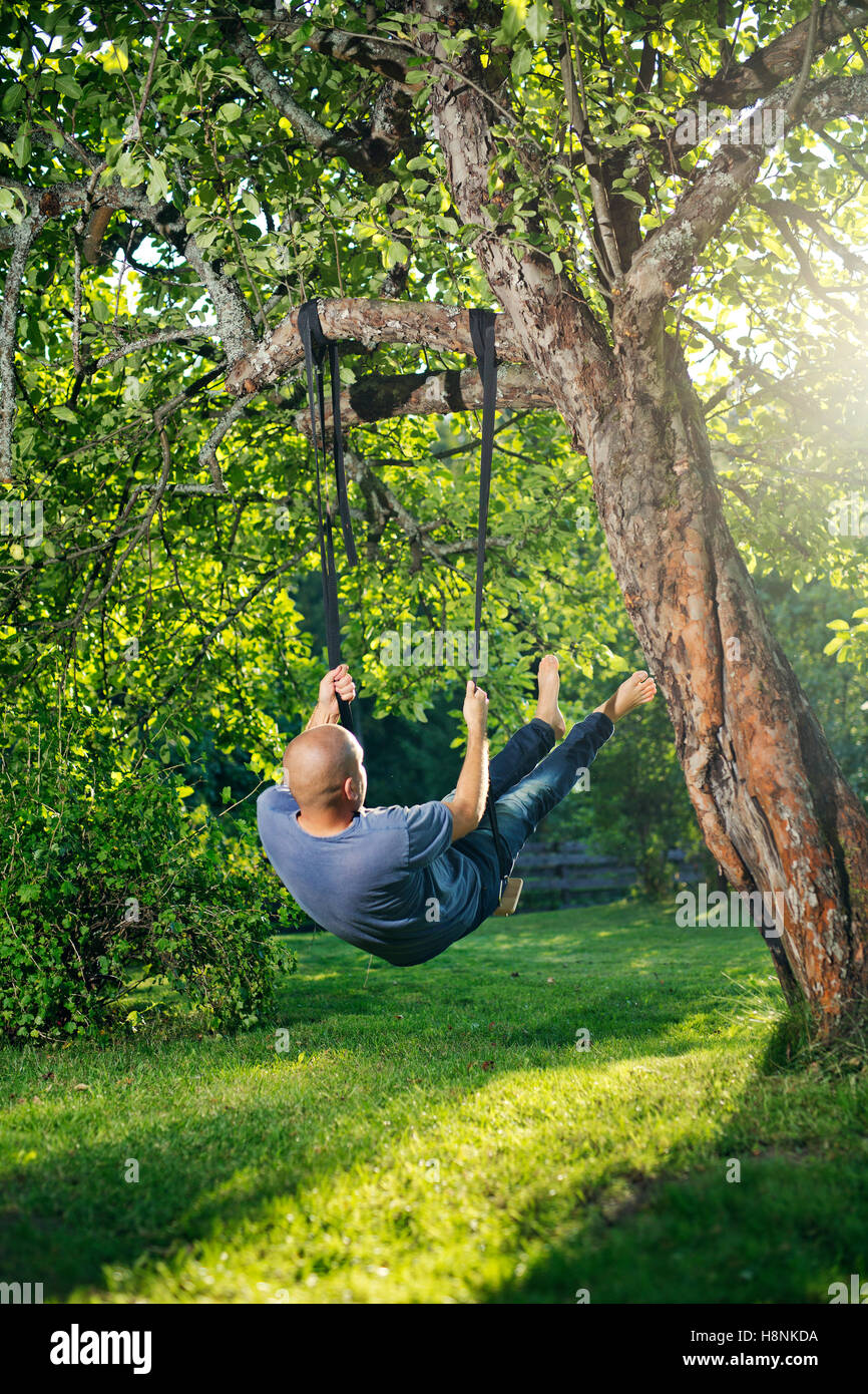 Man swinging on tree swing - Stock Image