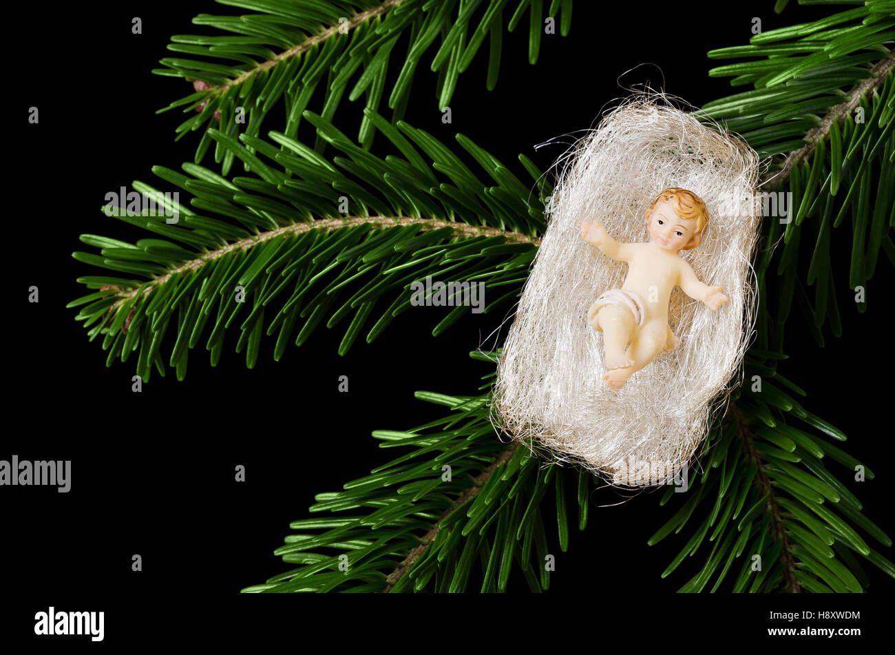 Christ Child Figurine In Angel Hair On A Fir Branch On Black Stock