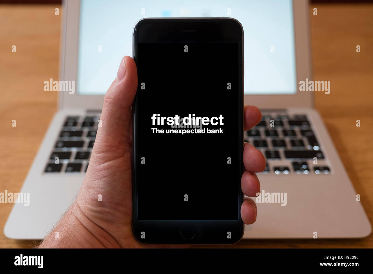 Using iPhone smart phone to display website logo of First Direct Bank Stock Photo