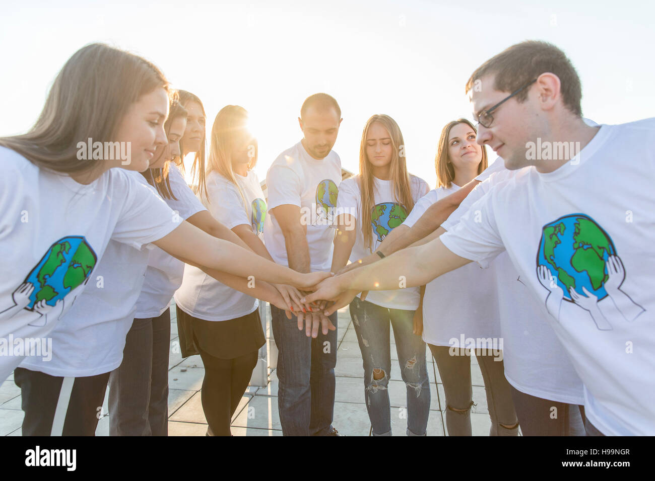 Group of teenage environmentalists joining hands in circle - Stock Image