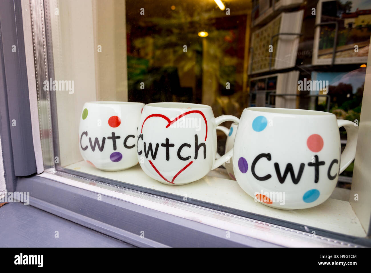 Three mugs with the Welsh language word Cwtch, meaning cuddle or hug in a shop window. Stock Photo