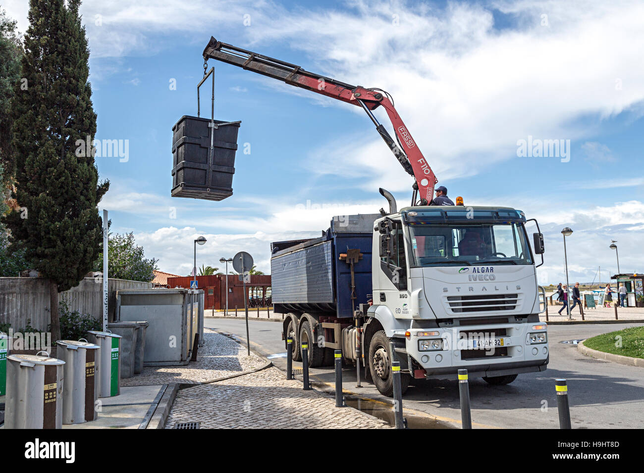 Lorry with lifting arm picking up recycling container, Alvor, Algarve, Portugal - Stock Image